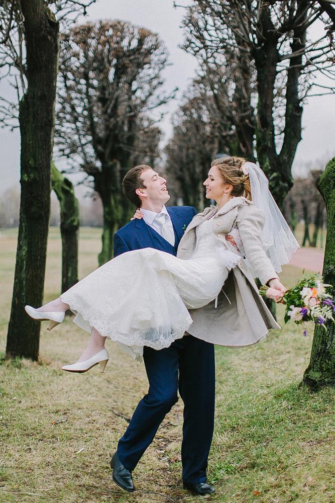 жених идет на руках с невестой