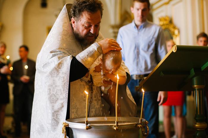 батюшка крестит